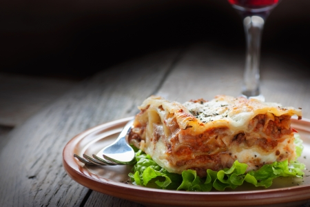 Italian cuisine  Freshly baked homemade lasagna with minced meat and cheese served on a piece of lettuce and red wine