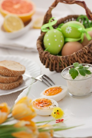 Traditional Easter breakfast. Table setting with Boiled eggs with ham, cottage cheese and Easter decorations photo