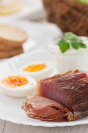 jamones: Tradicional desayuno de Pascua. Mesa con huevos con jamón, queso cottage y decoraciones de Pascua