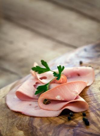 Italian salami mortadella on wooden olive background photo