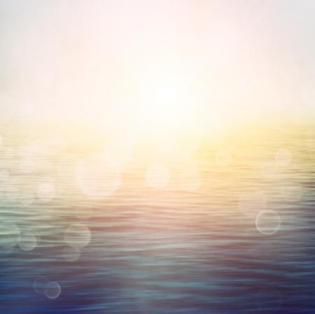 wschód słońca: Streszczenie latem charakter lub wiosna, oceanu, morze, tło Małe fale na powierzchni wody w ruchu rozmycia z bokeh światła od wschodu