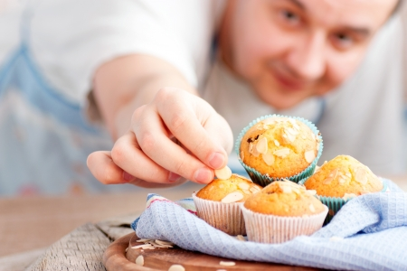 Chef is decorating delicious organic muffins  Almond and cherry cup cakes in natural setting  photo