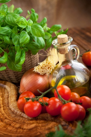 Fresh ingredients for italian cuisine: pasta, tomatoes, basil, olive oil, garlic and onion photo