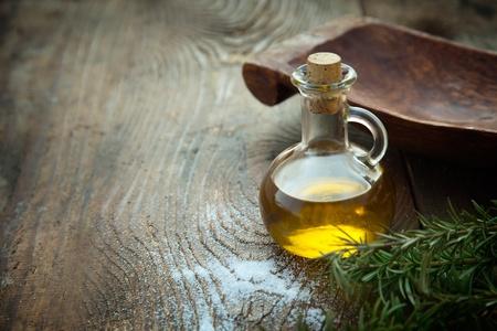 L'huile extra vierge d'olive saine avec le romarin frais sur fond de bois rustique Banque d'images
