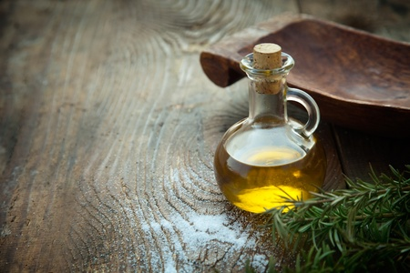 aceite de oliva: Virgen extra saludables del aceite de oliva con romero fresco en el fondo de madera rústica