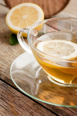 Cup of organic lemon fruit tea on nature wooden background photo
