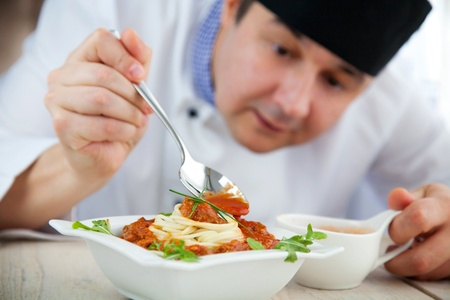 Male chef in restaurant kitchen is garnishing and preparing pasta dish photo