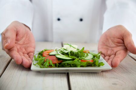 commercial kitchen: Male chef in restaurant kitchen is garnishing and preparing pasta dish Stock Photo