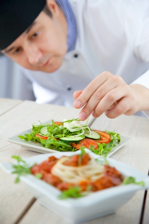 Male chef in restaurant kitchen is garnishing and preparing pasta dish Imagens