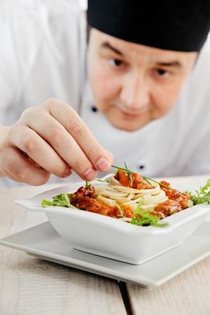 chef cocinando: Chef de cocina del restaurante en el Hombre est� embargando y la preparaci�n de un plato de pasta Foto de archivo