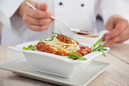 Male chef in restaurant kitchen is garnishing and preparing pasta dish photo