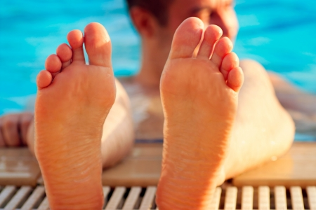 soaking: Holiday concept with man soaking feet in swimming pool. Stock Photo