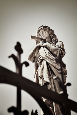 Vintage image of an old Religious statue in the old cemetery photo