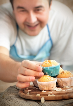 Happy baking. Chef is decorating delicious organic muffins. Almond and cherry cup cakes in natural setting. photo