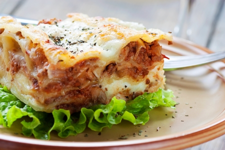 lasagna: Italian cuisine. Freshly baked homemade lasagna with minced meat and cheese served on a piece of lettuce and red wine.