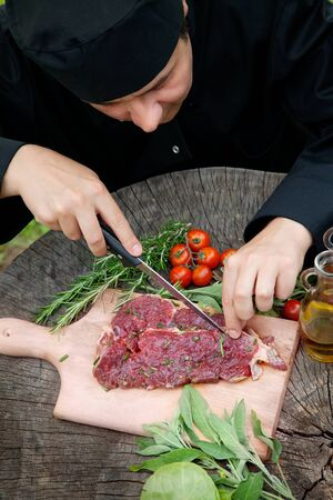 Cooking ingredients  marinated meat,oil,vinegar, herbs and vegetables  Chef is carving and marinating meat  photo