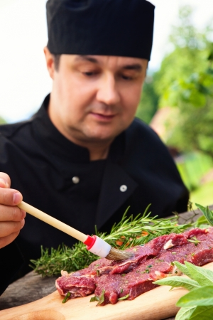 barbecue party: Cooking ingredients: marinated meat,oil,vinegar, herbs and vegetables. Chef is carving and marinating meat.