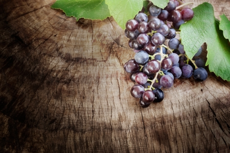 Freshly harvested Black grapes on wooden background with copyspace photo