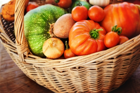 Freshly harvested summer vegetables in large basket with garden scissors  Pumpkin, large tomatoes, cherry tomatoes, onion, cucumber, garlic and potato photo
