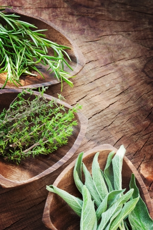 Fresh aromatic herbs on old wooden background  Rosemary, thyme and sage Stock Photo