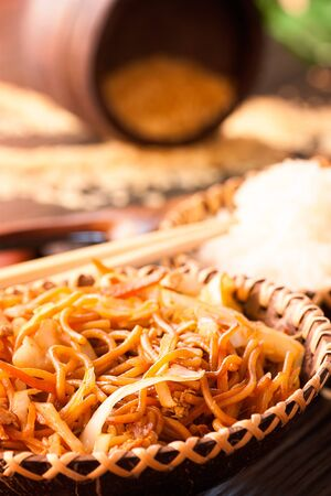 egg roll: Chinese food. Egg noodles with chicken and vegetables, steamed rice and soy sauce.