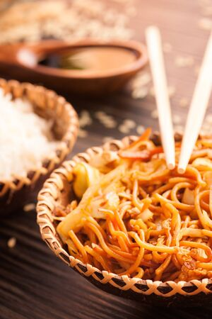 Chinese food. Egg noodles with chicken and vegetables, steamed rice and soy sauce. photo
