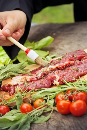 Cooking ingredients: marinated meat,oil,vinegar, herbs and vegetables. Chef is carving and marinating meat. photo