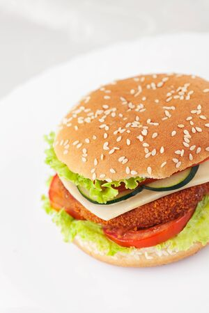 chicken burger: Junk food concept. Deep fried chicken or fish burger sandwich with lettuce, tomato, cheese and cucumber on wooden background. Stock Photo