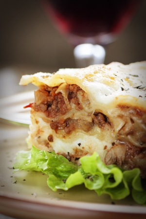 Italian cuisine. Freshly baked homemade lasagna with minced meat and cheese served on a piece of lettuce and red wine. photo