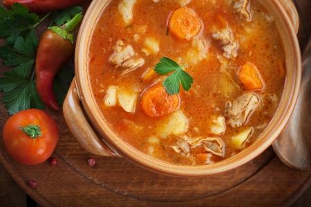 Läckra kalvkött gryta soppa med kött och grönsaker på trä Stockfoto