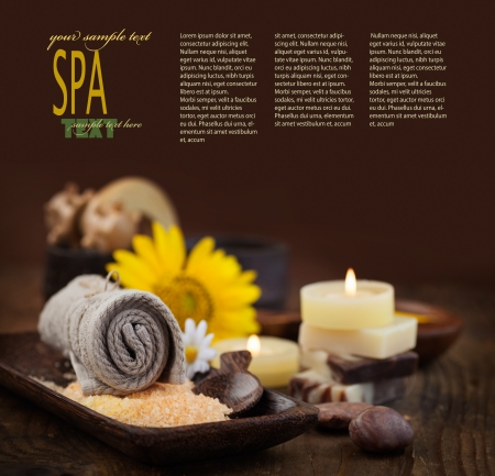 natural setting: Spa and wellness setting with natural bath salt, candles and towel, massager and sunflower.. Brown dayspa nature set with copyspace Stock Photo