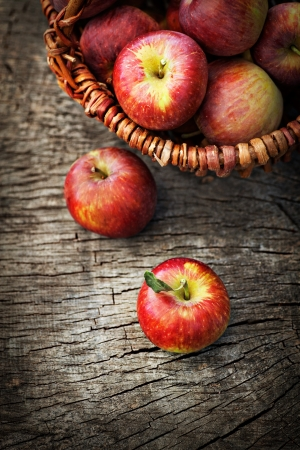 apple pie: Fresh harvest of apples. Nature theme with red grapes and basket on wooden background. Nature fruit concept. Stock Photo