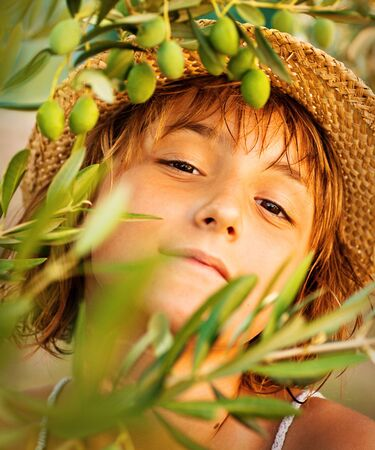 Beautiful little girl in summer olive tree garden. Child nature concept background. Olive harvest photo