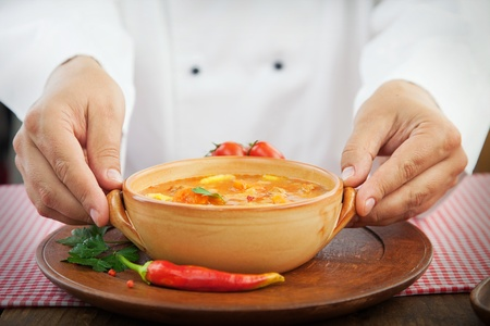 culinary skills: Hotel restaurant concept. Chef is finishing presenting stew dish with spices and garnish Stock Photo