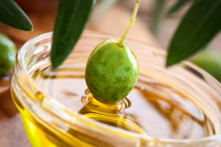 Extra virgin healthy Olive oil with fresh olives on rustic wooden background Stock Photo