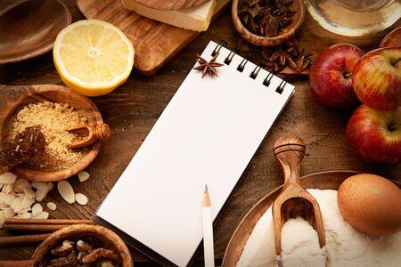 Bakning konceptet bakgrund med papper för anteckningar. Jul och vinter cookies ingredients.Baking bakverk och kakor: äpplen, kryddor, socker, ägg på trä