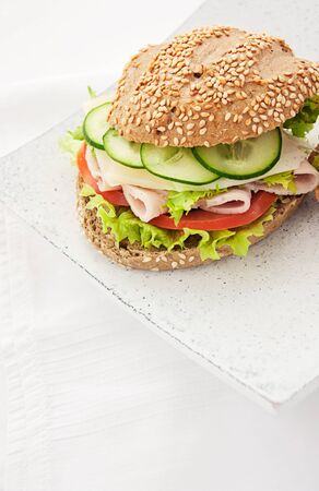 Delicious ham, cheese and salami sandwich with vegetables, lettuce, cherry tomatoes photo