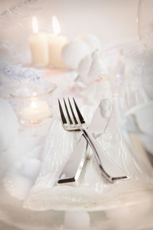 Christmas table setting  Fork and knife in elegant holiday setting with snow and white ornaments photo