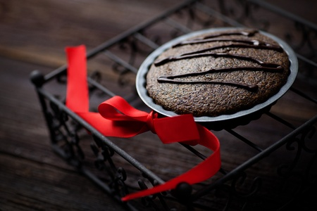 souffle: Chocolate cake. Souffle with red ribbot on wood.