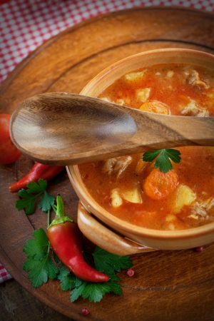 goulash: Delicious veal stew soup with meat and vegetables on wood. Stock Photo