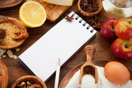 baking ingredients: Baking concept background with paper for notes. Christmas and winter  cookies ingredients.Baking pastry and cookies: apples, spices, sugar, eggs on wood