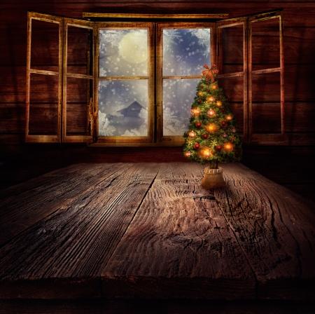 Juldesign - julgran. Xmas vintern bakgrund i trä stuga med julgran och fönster med vinternatt i bakgrunden. Stockfoto