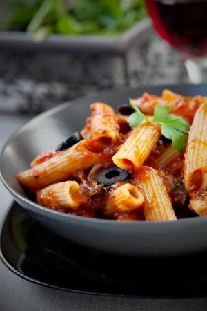 La cuisine italienne. P�tes penne � la sauce tomate, les olives et d�corer