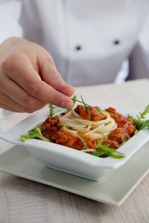 aceite de cocina: Cocinero de sexo masculino en la cocina del restaurante est� embargando y la preparaci�n de un plato de pasta
