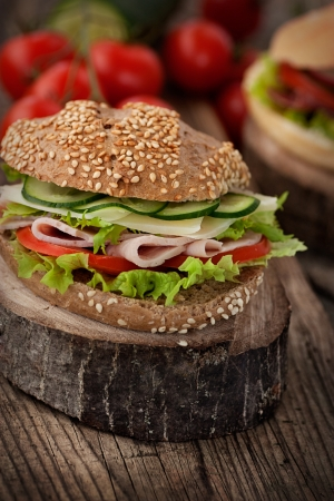 Delicious ham, cheese and salami sandwich with vegetables, lettuce, cherry tomatoes in natural setting with wooden background photo