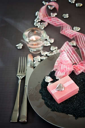 Restaurant series. Valentines day dinner with table setting in pink and gray and holiday elegant heart ornaments photo