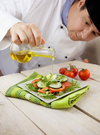 garnish: Food concept. Chef is pouring olive oil over fresh salad in restaurant kitchen.