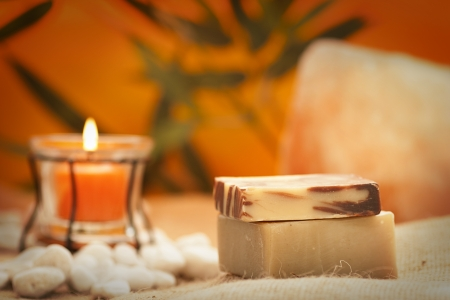 dayspa: Spa setting in orange tones with candles  Natural organic soap Stock Photo
