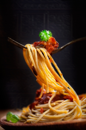 bolognese: Italian food  Pasta spaghetti with tomato sauce, olives and garnish  Pasta macro on fork Stock Photo