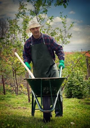 carretilla: Spring Garden Hombre concepto está haciendo trabajos de jardinería con carretilla